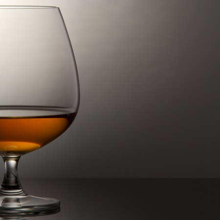 Glass of brandy over grey background photo