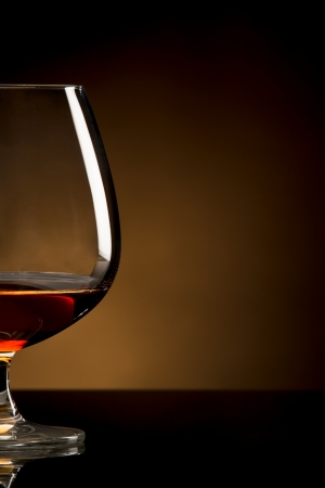 cognac: Glass of brandy over brown background