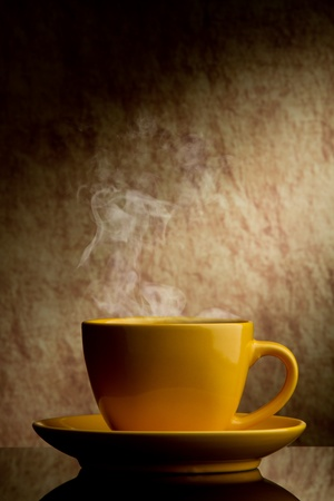 freshening: yellow cup of coffee  on a old stone background. Stock Photo