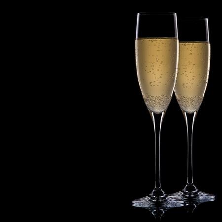 dwarsfluit: Een glas champagne, geïsoleerd op een zwarte achtergrond.