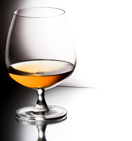 Glass of brandy over white background Stock Photo