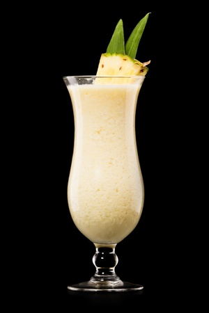 Pina colada drink cocktail glass isolated on black background photo
