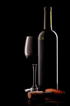red wine pouring: white bottle with red wine and glass and cork with a corkscrew on a black