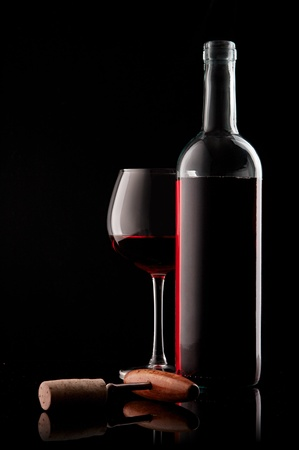 wine and food: white bottle with red wine and glass and cork with a corkscrew on a black