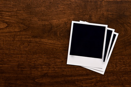 Empty instant photos on wooden table background Stock Photo - 10693562