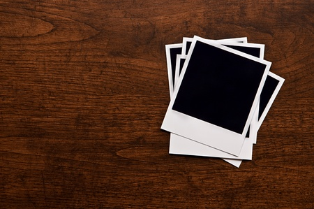 Empty instant photos on wooden table background photo