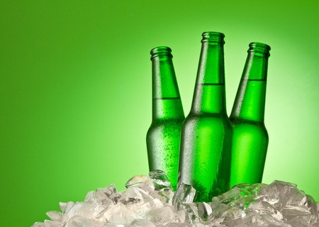 brown bottle: Three beer bottles getting cool in ice cubes. Isolated on a green.