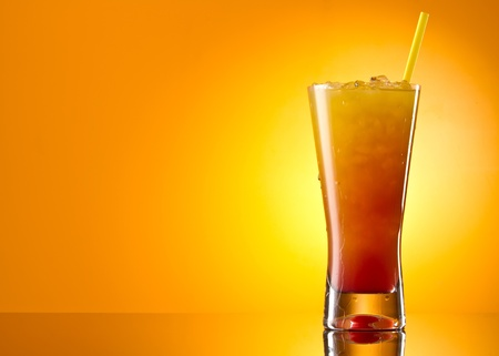 Tequila sunrise Cocktail isolated on a orange background photo