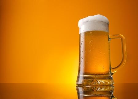 Bicchiere di birra close-up con schiuma su sfondo arancione