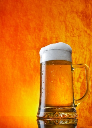 Glass of beer close-up with froth over orange background photo