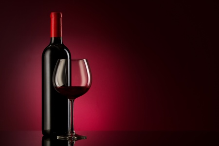 bottle with red wine and glass on a red gradient photo