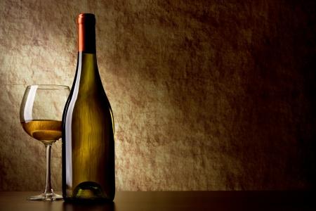 Flasche mit Weißwein und Glas auf einem alten Stein. Flasche im Vordergrund