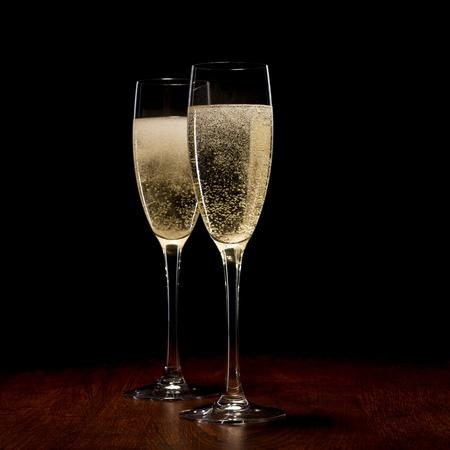 dwarsfluit: twee glazen met champagne op een houten tafel