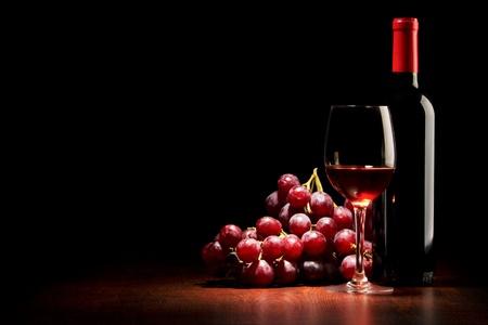 wine pouring: Bicchiere di vino e la bottiglia e l'uva rossa su un tavolo in legno