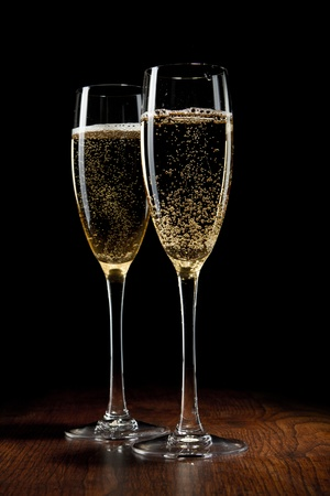 champagne flutes: two glass with champagne on a wooden table