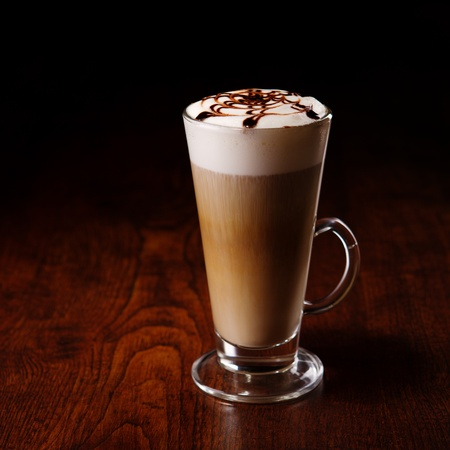 capuccino: latte mug on a wooden table with a spoon and sugar
