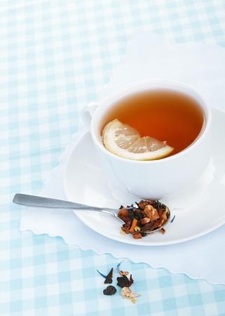 hot fruit tea with lemon on a blue tablecloth photo