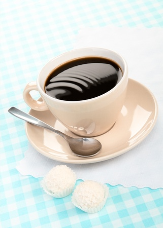 black coffee with coconut candies on a blue tablecloth photo