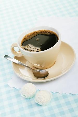 tarde de cafe: café negro con dulce de coco en un mantel azul