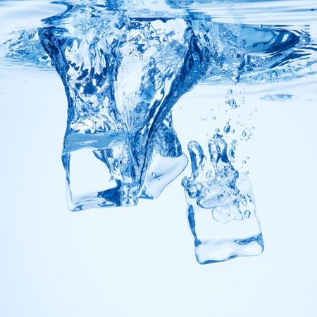 A background of bubbles forming in blue water after ice cubes are dropped into it.