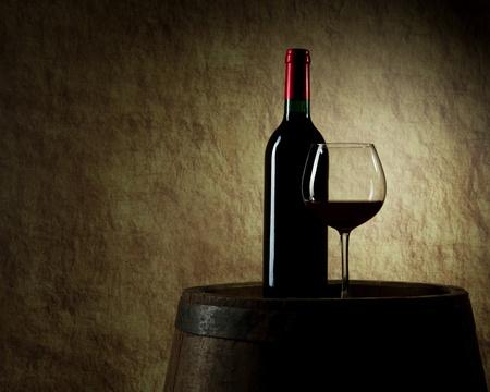 cave: la nature morte avec du vin rouge, bouteille, verre et vieux tonneau