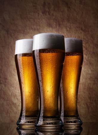material de vidrio: Tres cerveza fr�a en un vaso sobre una piedra antigua