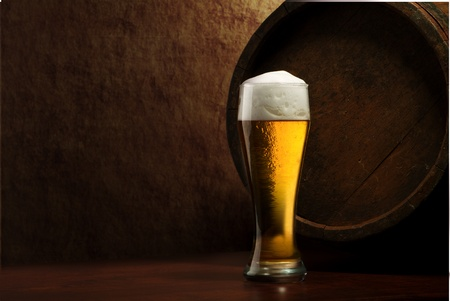 beer background: Beer into glass on a old stone and old barrel Stock Photo