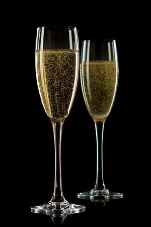 Ein Glas Champagner, auf einem schwarzen Hintergrund. Lizenzfreie Bilder