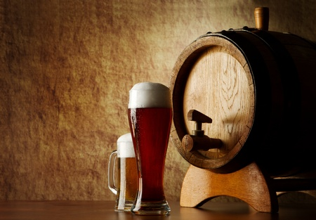pub food: Beer into glass on a old stone and old barrel Stock Photo