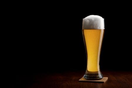 Bier in Glas auf einem schwarzen und Holztisch