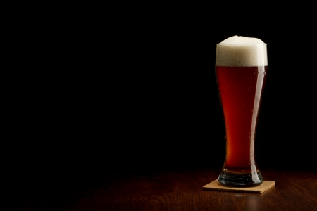 glass of beer: Beer into glass on a black and wooden table