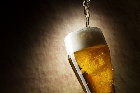 beer drinking: Beer into glass on a old stone