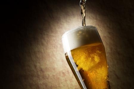botellas de cerveza: La cerveza en un vaso sobre una piedra antigua