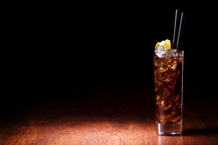 Cocktail with cola on a wooden table