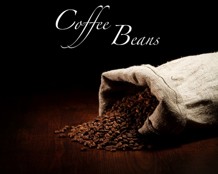 Burlap sack of coffee beans against dark wood background Standard-Bild