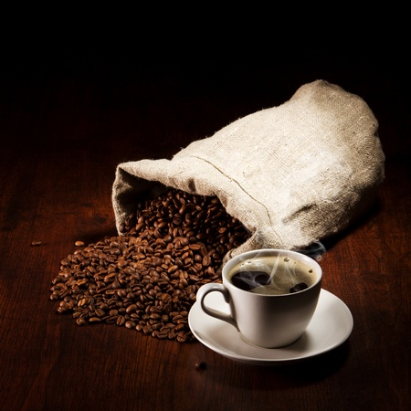 brew: Coffee cup with burlap sack of roasted beans on rustic table