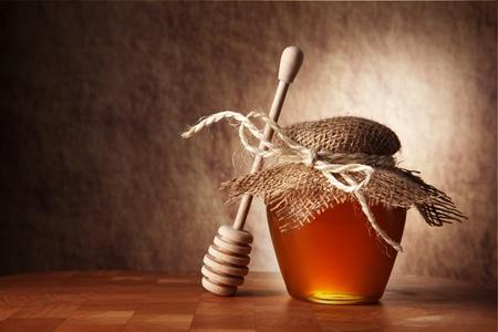 Topf Honig und Holzstäbchen sind auf einem Tisch.