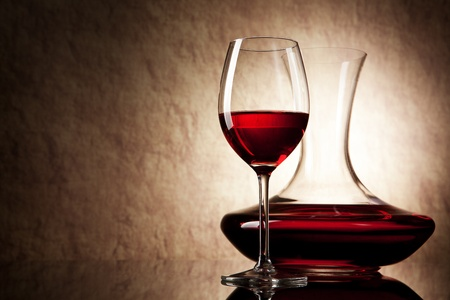decanter with red wine and glass on a old stone background Standard-Bild