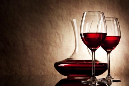 Karaffe mit Rotwein und Glas auf einem alten Stein Hintergrund