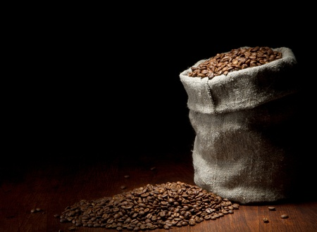 coffee sack: Burlap sack of coffee beans against dark wood background Stock Photo