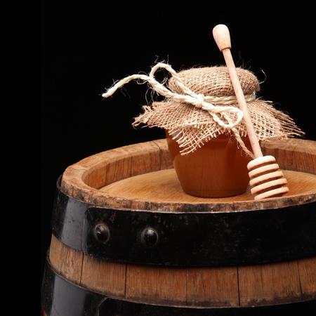 barell: honey pot and honey stick ona wooden barell