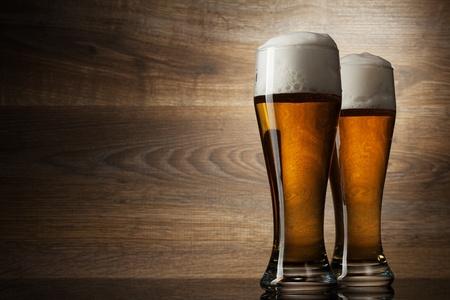 vasos de cerveza: Dos vaso de cerveza en el fondo de madera con copyspace