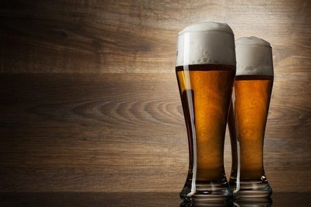 mug of ale: Two glass beer on wood background with copyspace