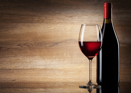 translucent red: Wine glass and Bottle on a wooden background