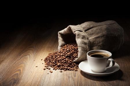 Kaffeetasse mit Sack von gerösteten Bohnen auf rustikalem Tisch