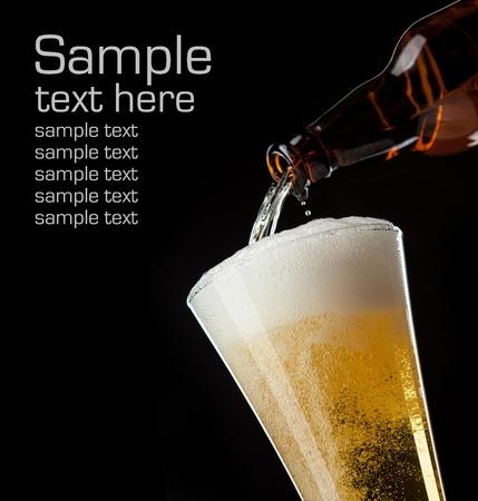 cerveza negra: vaso de cerveza y una botella sobre un fondo negro