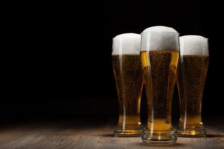 drei Glas Bier auf Holztisch mit copyspace
