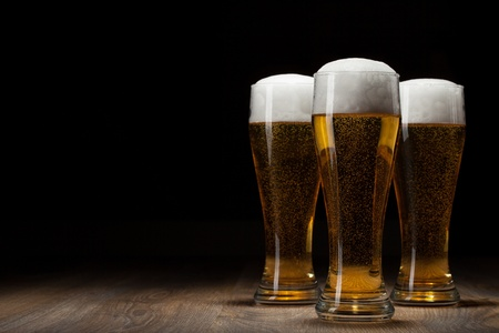 wino: three glass beer on wooden table with copyspace Stock Photo