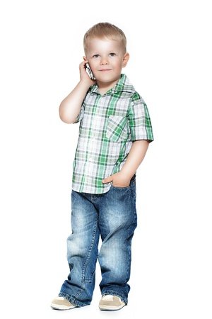 a little boy talking on the phone  isolated on white photo