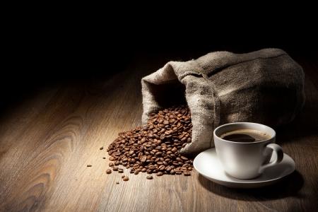 drinking coffee: Taza de caf� con saco de arpillera de granos tostados de mesa r�stica Foto de archivo
